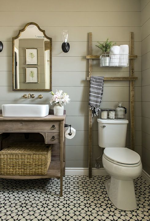 bathroom, patterned floor tiles, brown wooden planks, white toilet, wooden vanity, white sink