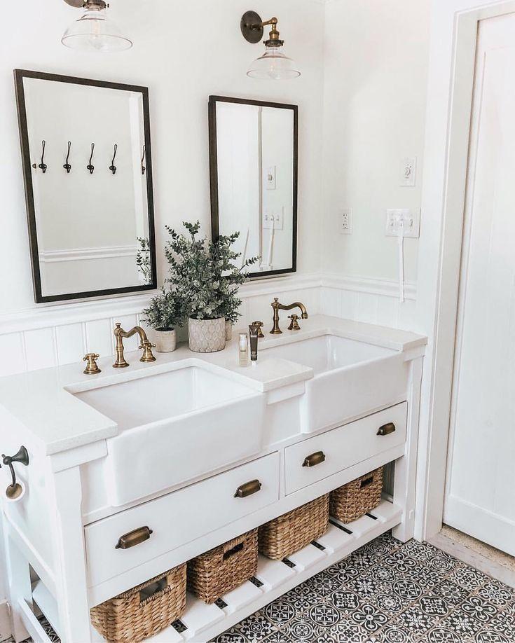 bathroom, patterned floor tiles, white wall, white wooden vanity, white drawers, white apron sink, white wainscoting, black framed mirror, glass sconces