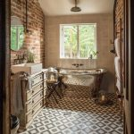 Bathroom, Patterned Square Floor Tiles, Exposed Brick Wall, White Wall, Stainless Tub, Wooden Cabinet, Round Mirror, Pendant, Rack On The Wall