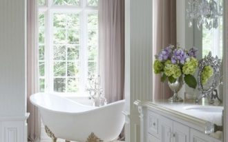 bathroom, white floor, white wall, white cabinet, sconce, white tub with golden claw feet