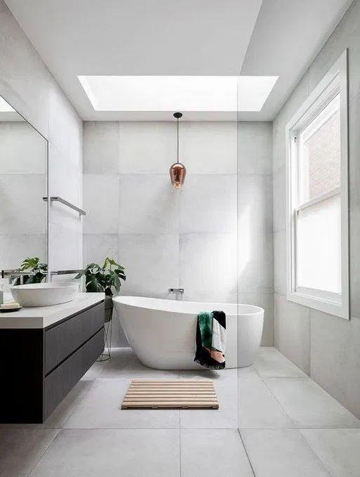 bathroom, white floor, white wall, white tub, black floating cabinet, white counter top, white sink, glass ceiling window, golden pendant