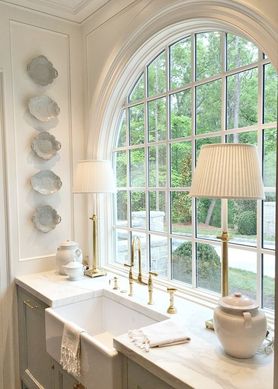 bathroom, white marble counter top, large round mirror, white cabinet, white table lamp