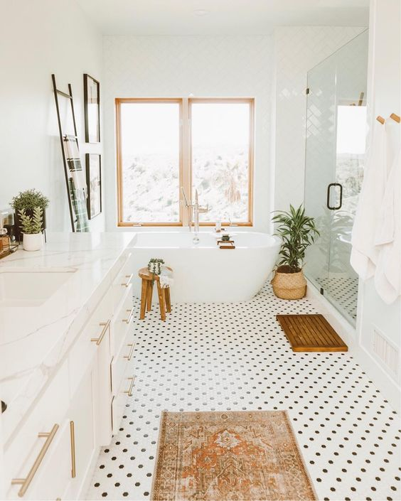 bathroom, white polka dot patterned floor, white tub, white wall, white cabinet with white marble top, glass partition