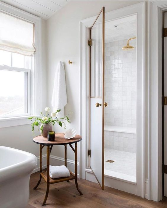 bathroom, white square tiles, a room for shower, golden faucet, round table, wooden floor, white tub
