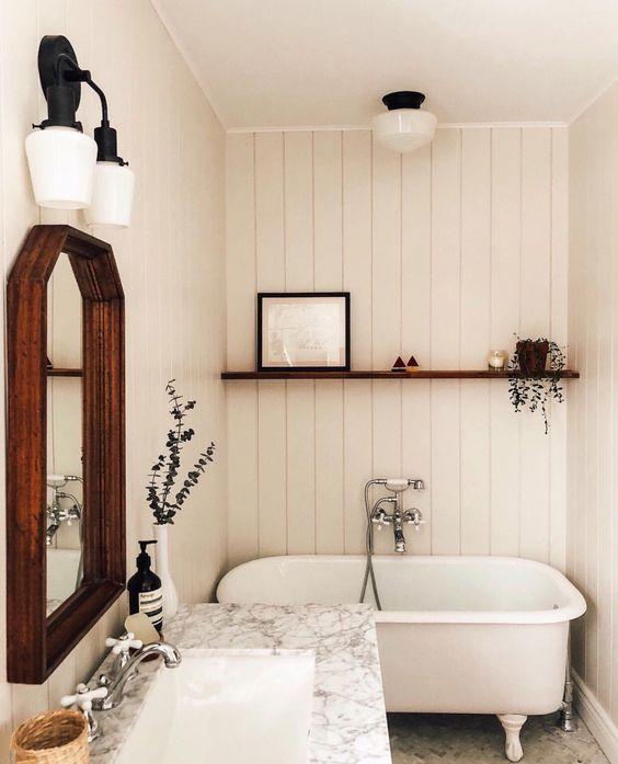 bathroom, white vertical planks, white marble vanity top, white marble floor, dark wooden framed mirror, white sconces, floatig wooden shelves, white tub with white claw feet