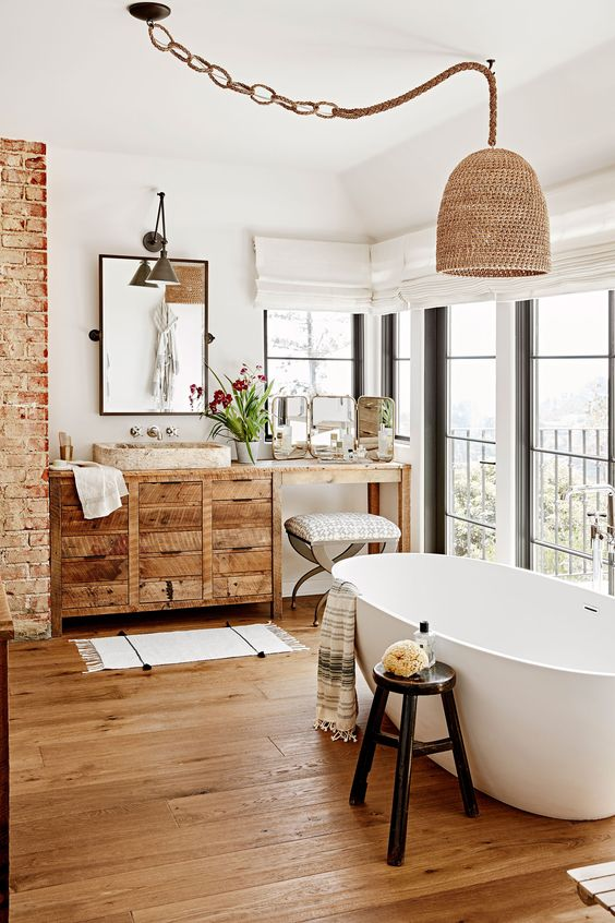 bathroom, white wall, brick exposed wall, wooden cabinet, brown marble sink, wooden floor, white tub, rattan pendant, glass windows