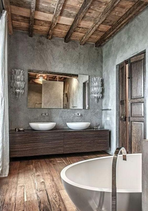 bathroom, wooden floor, grey wall, dark wooden cabinet, white sinks, white bowl tub, stainless faucet, sconces, wooden ceiling with wooden beams