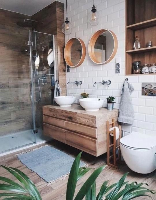 bathroom, wooden floor, wooden wall, white subway wall tiles, round framed mirror, floating wooden cabinet, white bowl sink, white toilet, wooden indented shelves
