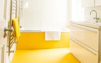 bathroom, yellow rubber flooring, white wal, white herringbone wall, white table, white vanity
