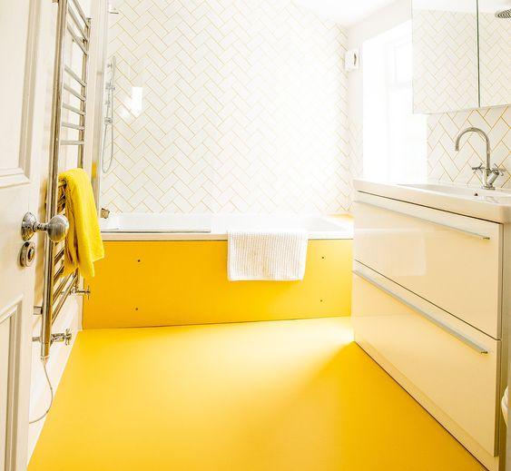bathroom, yellow rubber flooring, white wal, white herringbone wall, white table, white vanity