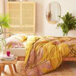 Bedroom, Orange Rug, White Wall, Rattan Cupboard, Wooden Platform, Yellow Bedding, Wooden Side Table, Mirror