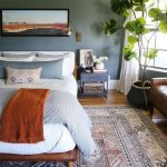 Bedroom, Wooden Floor, Blue Grey Wall, Wooden Platform, Brown Leather Sofa, Patterned Rug, Plants