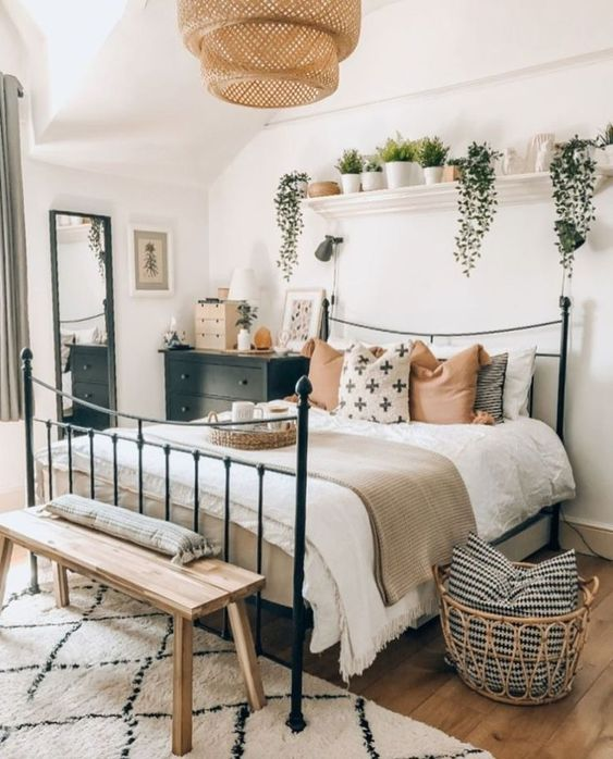 bedroom, wooden floor, white wall, black metal bed platform, wooden bench, black bedside cabinet, white floating shelves, rattan pendant, white rug