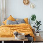 Bedroom, Wooden Floor, White Wall, Grey Platform, Yellow Bedding, Wooden Bench, Ratan Bench