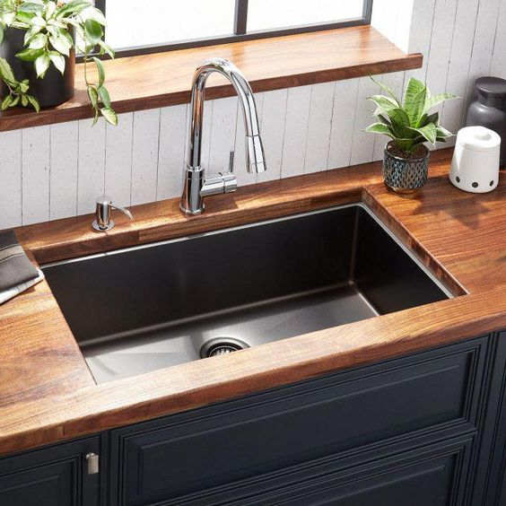 black undermounted sink, wooden counter top, stainless faucet, black cabinet, white vertical wooden wall, wooden window sill
