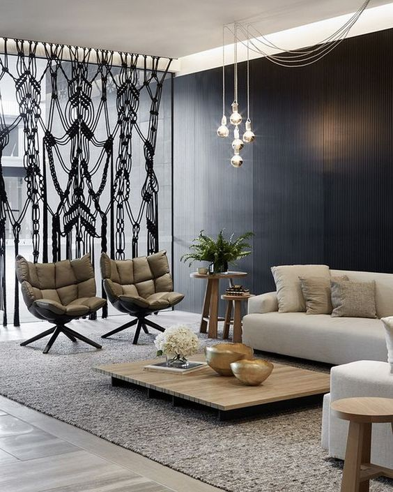 black wall, grey floor, grey rug, low wooden coffee table, white sofa, metalic pendants, grey chairs, wooden stool