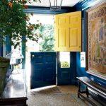 Blue Entrance, Wooden Floor, Patterned Rug, Blue Wall, Blue Door, Yellow Door, Black Pendant, Wooden Cabinet