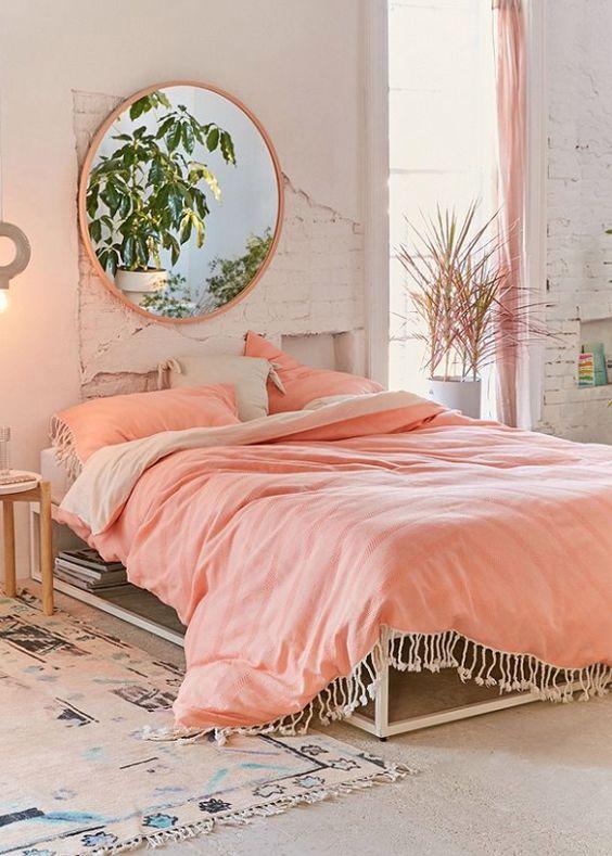 bohemian bedroom, peach bedding, cream platform, rug, pink round mirror, peach curtain, white exposed wall