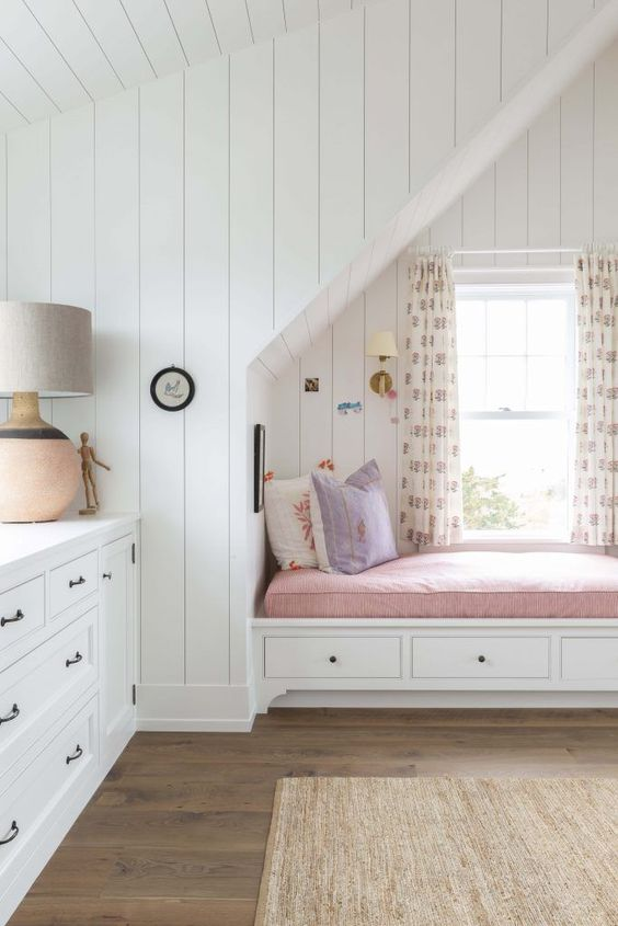 children's bedroom, wooden floor, white wooden planks on te wall, white wooden cabinet, white floating wooden bench, pink cushion, white curtain, sconce