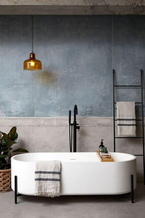 concrete floor, grey wall, golden pendant, white long tub, black faucet, black rack