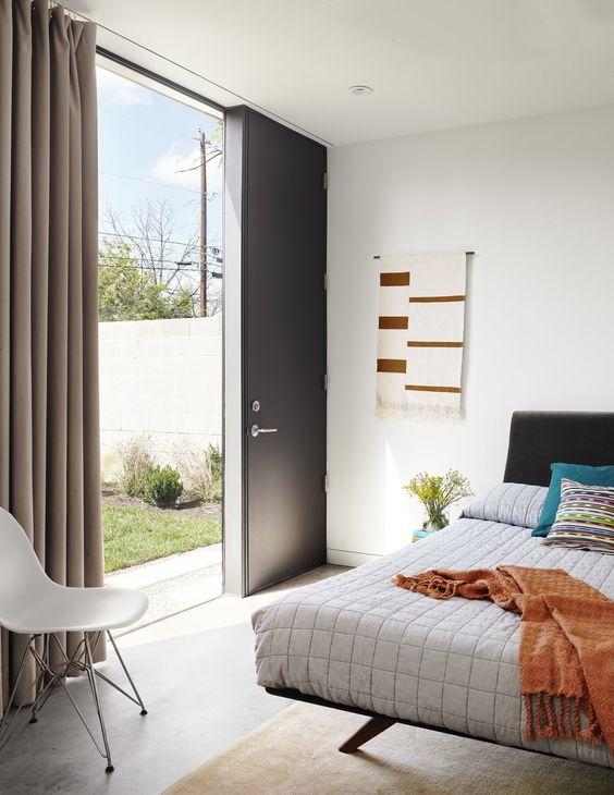 concrete floor, white wall, black headboard, white bedding, white midcentury modern chair, black door, large glass window