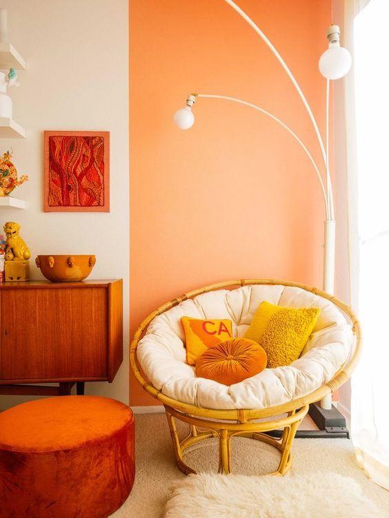 corner room, white orange wall, white bulb floor lamps, rattan chair, brown rug, orange ottoman, wooden cabinet