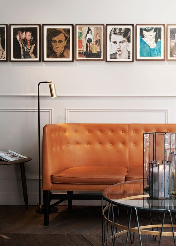 curvy lean orange sofa with tufted, white wainscoting, glass round coffee table, black floor lamp