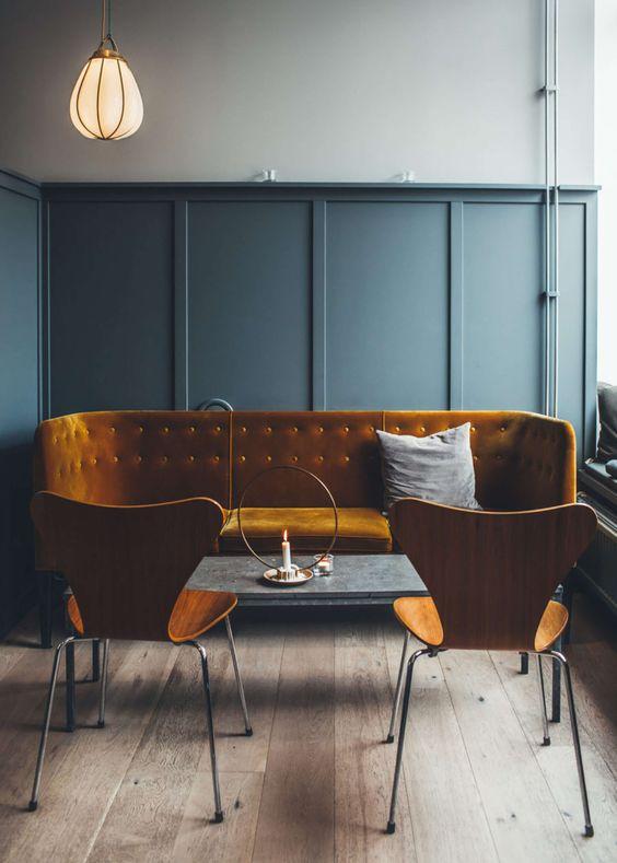 dark warm orange sofa and chairs, mint green wainscoting, grey wall, grey marble coffee table, wooden floor, orange pendant