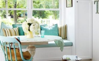 dining nook, patterned floor, white wall, white cabinet, white bench, blue cushion, blue pillows, blue chair, white tulip table