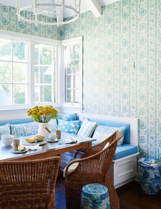 dining nook, wooden floor, blue wallpaper, white bench with blue cushion, blue pillows, rattan chairs, wooden table, white chandelier