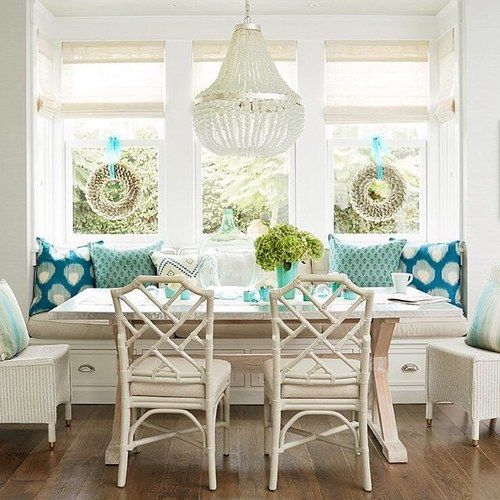 dining nook, wooden floor, white bench, white cushion, white rattan chairs, white marble table, white chandelier, blue pillows