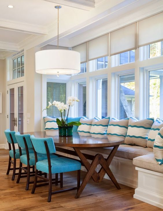dining nook, wooden floor, white wall, white round pendant, wooden oval table, white bench, brown cushion, white blue pillows, blue chairs