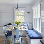 Dining Nook, Wooden Floor, White Wooden Bench, Blue Tufted Cushion, White Table, Blue Metal Chairs With Dark Blue Cushion, White Ship Lap, Glass Pendants,