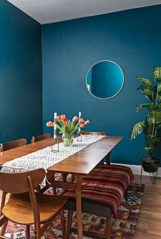 dining room, blue wall, wooden floor, wooden table, wooden chairs, wooden bench with green cushion, colorful rug