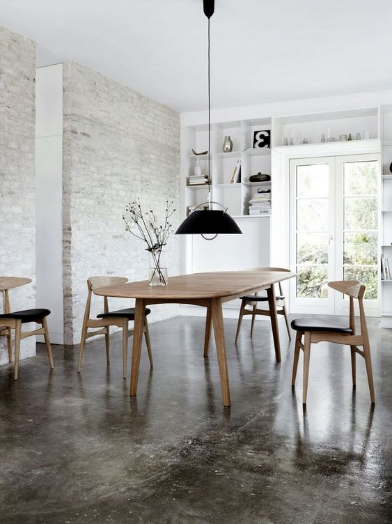 dining room, concrete floor, exposed white brick wall, black pendant, wooden table, wooden chairs, white built in shelves, glass door