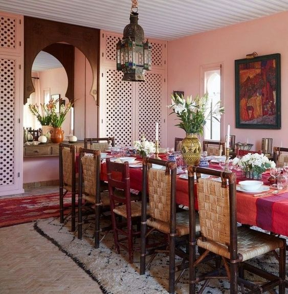 dining room, herringbone floor, pink wall, ret rug, white rug, red table, rattan chairs, moroccan pendant