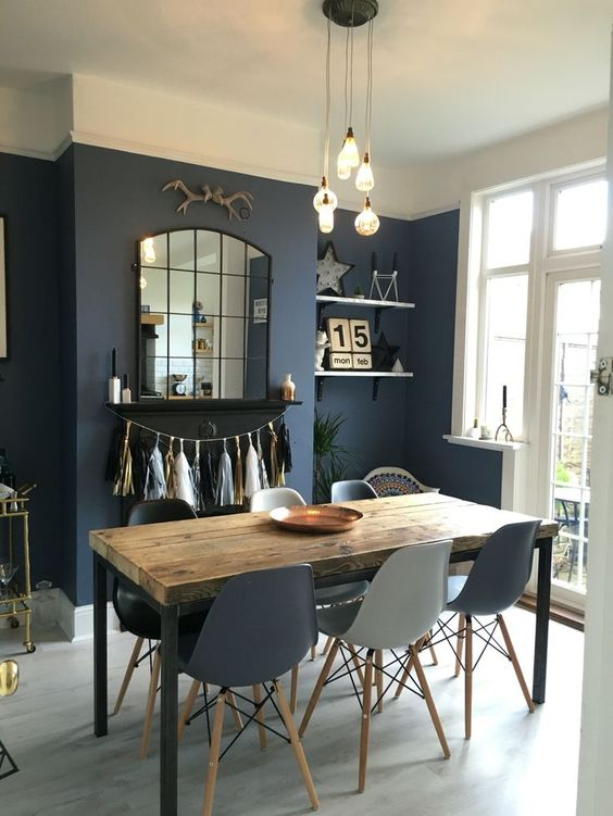 dining room, navy wall, grey floor, cream ceiling, yellow pendants, grey midcentury modern chairs, mirror, white framed door and window