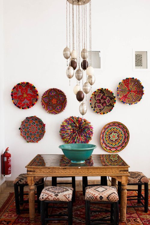 dining room, wooden floor, red rug, white wall, exotic chandelier, wooden table, patterned stool