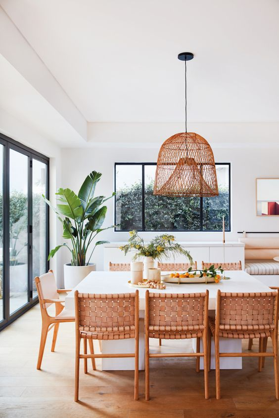 dining room, wooden floor, white wall, white table with sturdy legs, rattan chairs, wooden chair with white cushion, rattan pendant