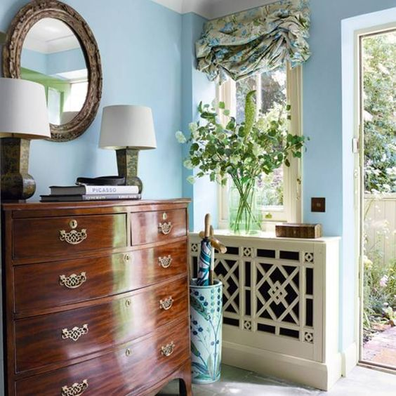 entrance, blue wall, strong brown wooden cabinet, round mirror, blue curtain, white table lamp