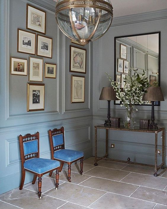 entrance, brown floor tiles, light blue wall wainscoting, pictures, glass pendant, thin console table, mirror