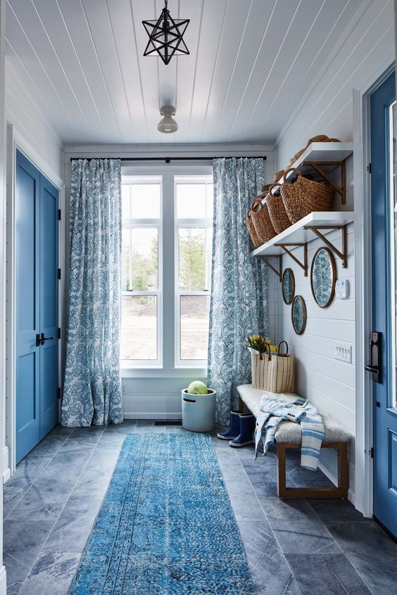 entrance, grey floor, blue long rug, white shiplap, blue door, white floating shelves, wooden bench with white cushion, blue curtain, star pendant