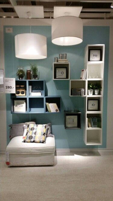 floating shelves in white and blue squares, white rug, white square ottoman, white round pendant