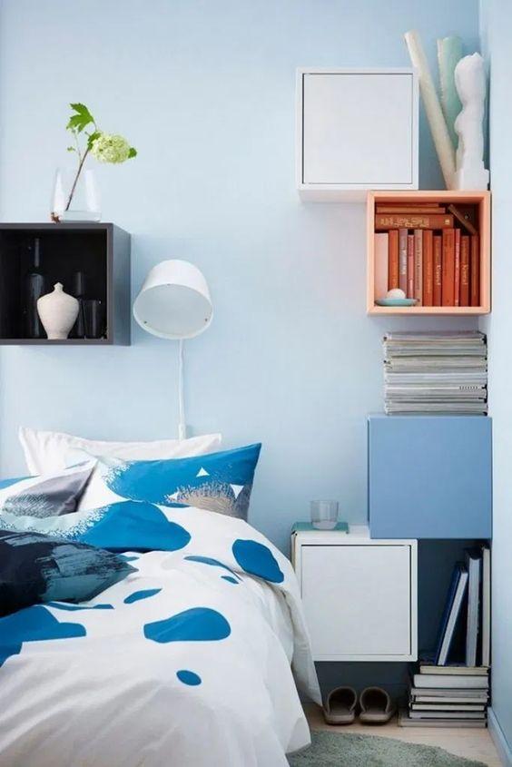 floating square boxes in orange, white, blue, blue wall, black shelves, white blue bedding, white table lamp, wooden floor