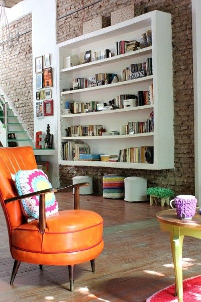 floating white wooden bookshelves, exposed brick wall, wooden floor, orange leather chair