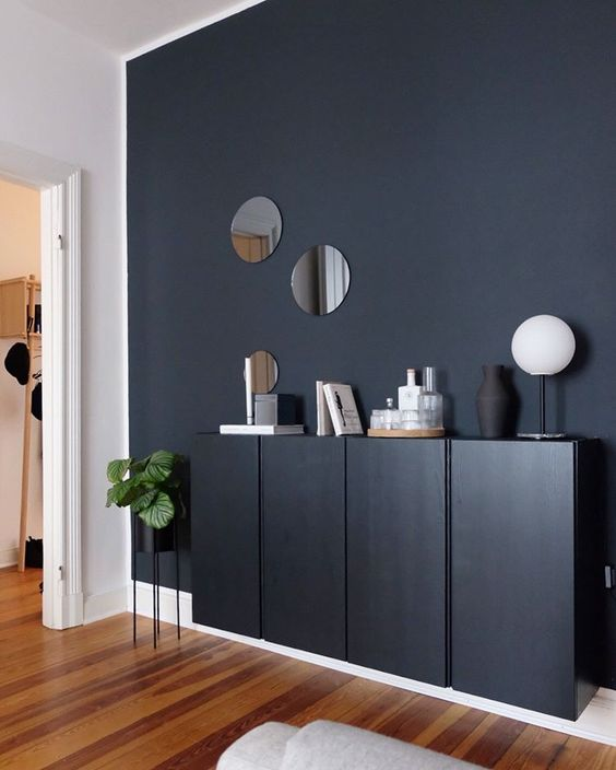 hallway, wooden floor, black accent wall, black cabinet, white wall
