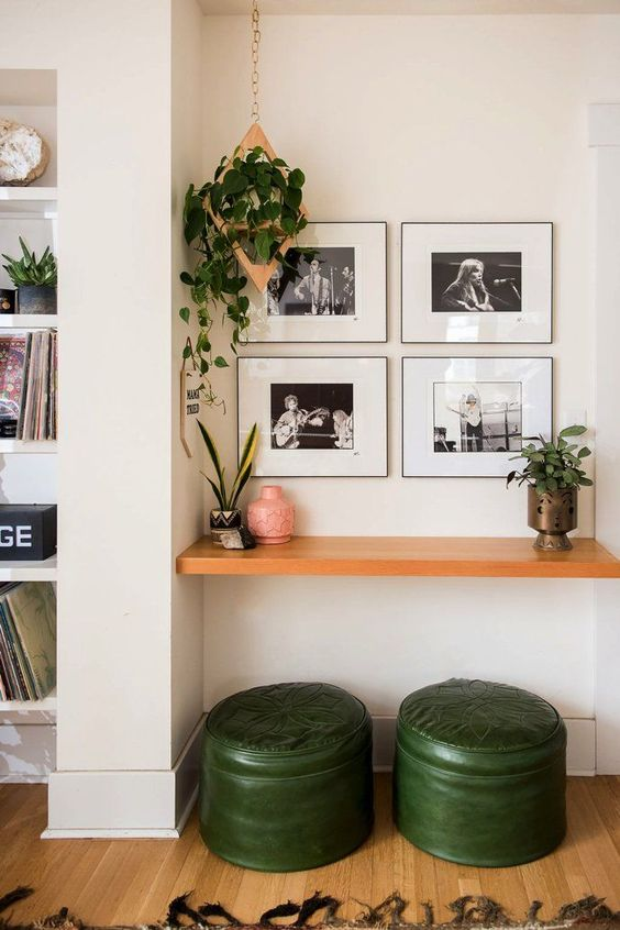 hallway, wooden floor, white wall, wooden floating table, green leather stools