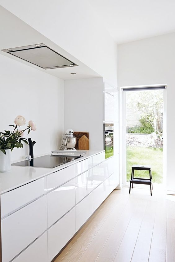 kichen, long space, wooden floor, glossy white cabinet, indented space, white wall, black stool