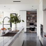 Kitchen, Concrete Floor, White Cabinet, White Island With Marble Top, White Corner Shelves, Floating Table, Black Chair