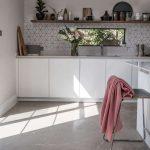 Kitchen, Concrete Floor, White Wall, White Bottom Cabinet, Hexagonal Backsplash, White Island, Floating Wooden Shelves